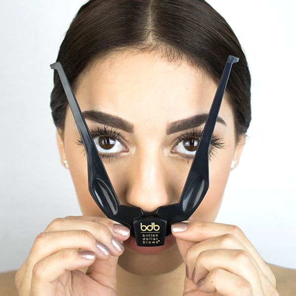 woman using the brow buddy tool from the best eyebrow kit