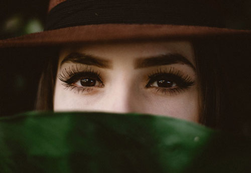 woman with long lashes and thick brows wearing a hat